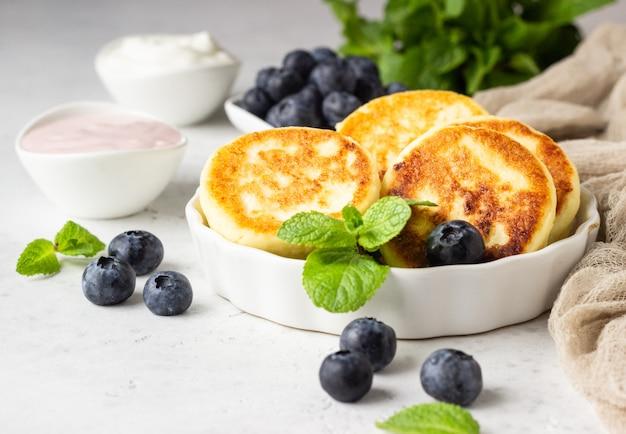 Bolinhos de queijo cottage com mirtilos, hortelã e molho.