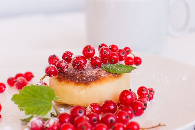 Bolinhos de queijo cottage syrniki com frutas de verão na chapa branca, fundo de mesa de madeira. panquecas de queijo russo com café da manhã doce.