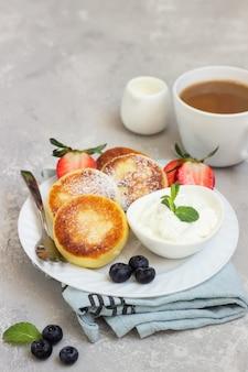 Bolinhos de queijo cottage (syrniki) servidos com creme de leite, frutas frescas (morango e mirtilo) e hortelã. pequeno-almoço saudável ou almoço de dieta.