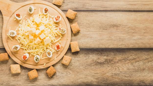 Bolinhos de queijo rodeado perto da tábua de madeira com queijo na mesa