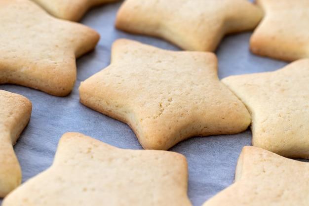 Bolinhos de shortbread assados em forma de estrelas em uma assadeira com papel manteiga recém-tirados do forno. lanche de chá no café da manhã. foco seletivo. vista de perto