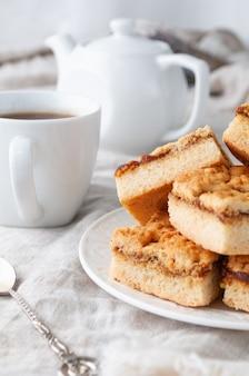 Bolinhos de shortbread caseiros recheados com geleia de maçã. em um prato branco. sobre uma toalha de mesa de linho de cor cinza. no fundo está um bule e uma xícara.