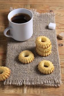 Bolinhos de shortbread e xícara de café sobre serapilheira e sobre fundo de madeira velho