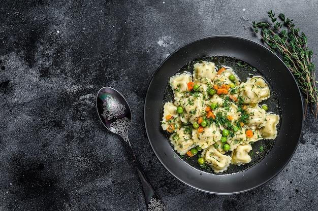 Bolinhos de sopa com macarrão ravioli em uma tigela com verduras. fundo preto. vista do topo. copie o espaço.