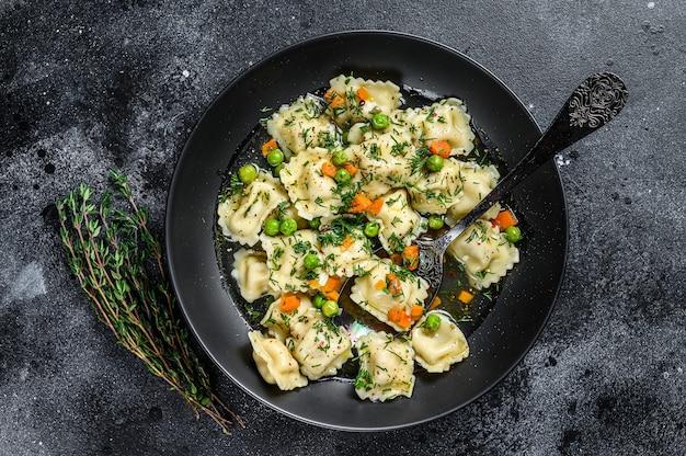 Bolinhos de sopa com macarrão ravioli em uma tigela com verduras. fundo preto. vista do topo.