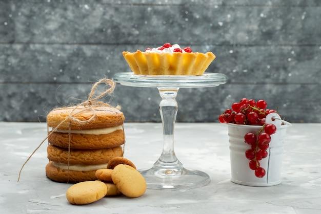 Bolinhos de vista frontal com biscoitos cremosos e cranberries vermelhos na superfície clara de frutas doces