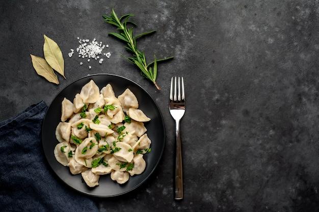 Bolinhos deliciosos de farinha de trigo integral caseiro ou bolinhos russos polvilhados com salsa fresca em um prato sobre uma mesa de madeira, cópia espaço, vista superior