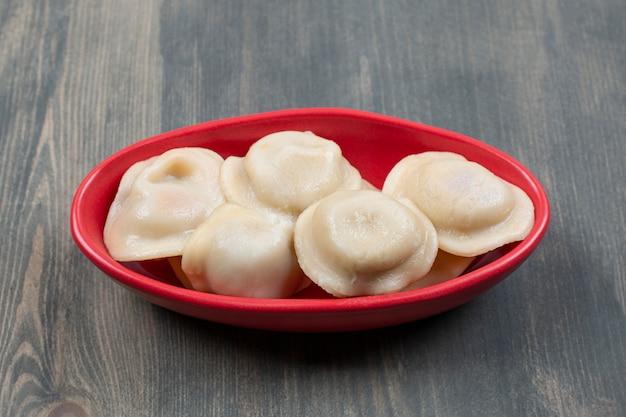 Bolinhos deliciosos em um prato vermelho sobre uma mesa de madeira