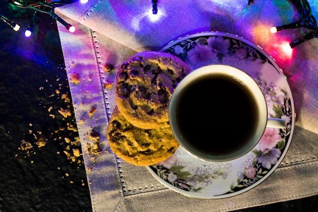 Bolinhos do chocolate e um copo do chá no fundo escuro com luzes coloridas.