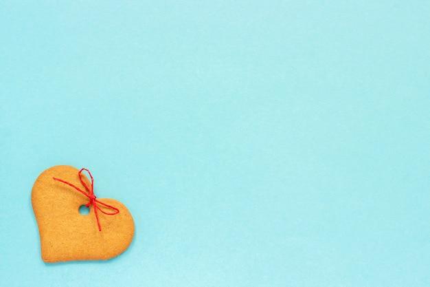 Bolinhos do gengibre coração-dados forma decorados com uma curva em um fundo azul.