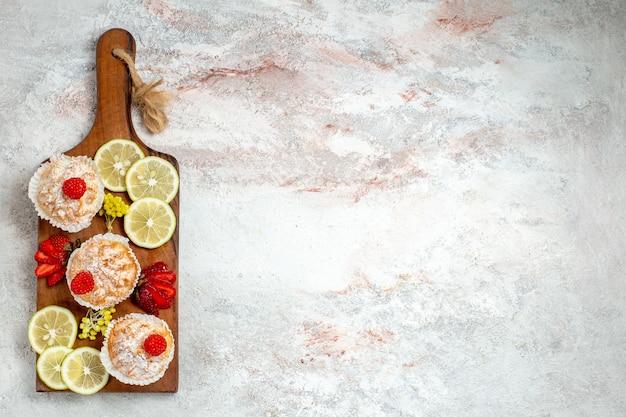 Bolinhos doces com rodelas de limão no fundo branco bolo de biscoito doce com frutas frescas cítricas