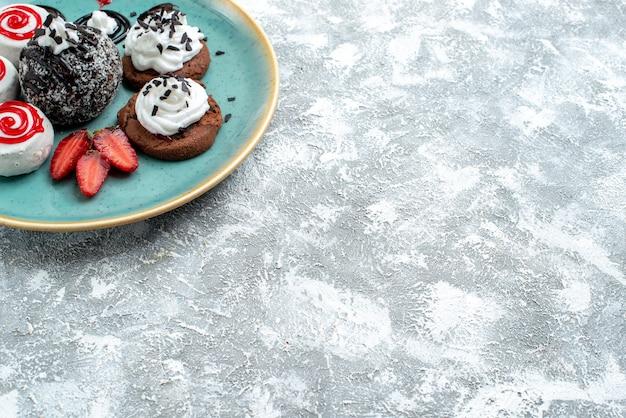 Bolinhos doces de vista frontal, biscoitos doces diferentes no espaço em branco