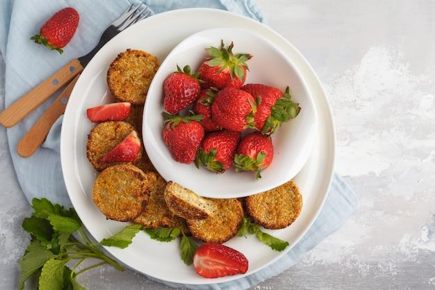 Bolinhos doces do tofu do vegetariano com morangos, vista superior. conceito de comida saudável vegan.