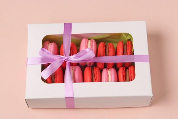 Bolinhos doces saborosos macaron, biscoito em uma caixa de presente branca em um rosa