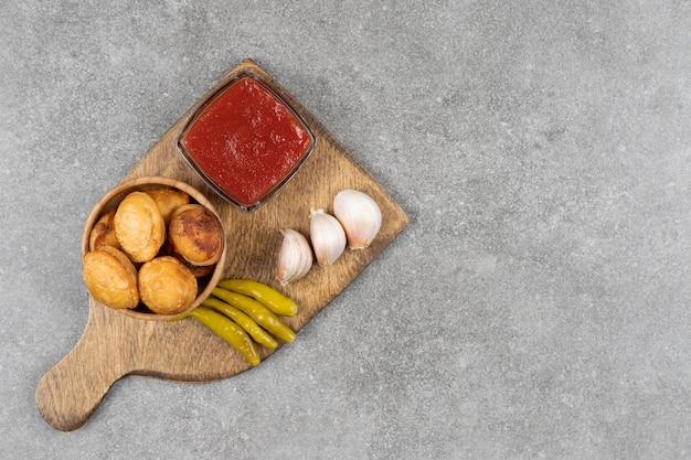 Bolinhos fritos e picles em tábua de madeira