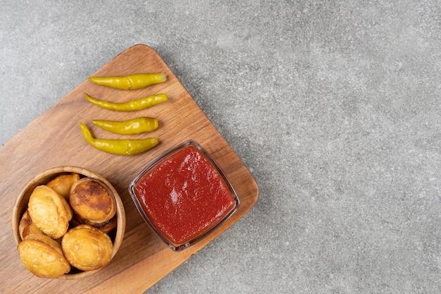 Bolinhos fritos e pimenta em conserva na tábua de madeira