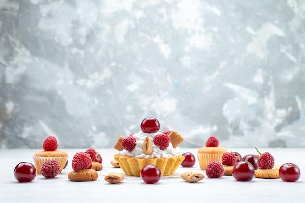 Bolinhos gostosos com framboesas e creme junto com biscoitos e bolos na luz