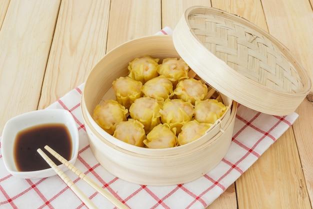 Bolinhos no vapor (dim sum chinês) em cesta de bambu em fundo de mesa de madeira