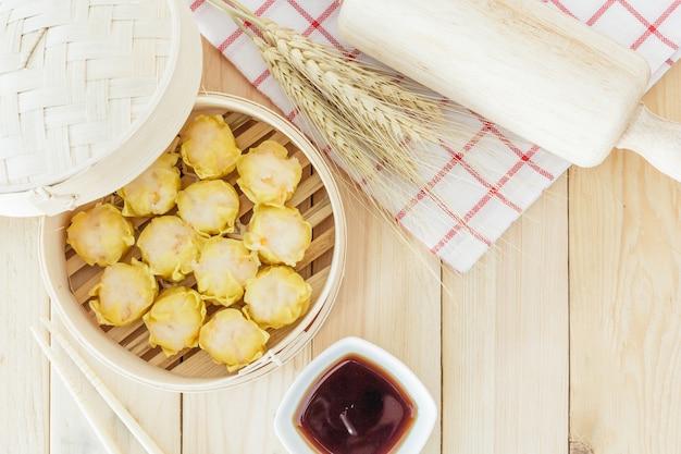 Bolinhos no vapor (dim sum chinês) na cesta de bambu, servir com pauzinhos na tabl de madeira