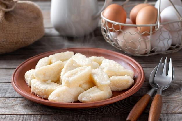 Bolinhos preguiçosos - vareniki de queijo cottage em um prato, close-up sobre fundo de madeira