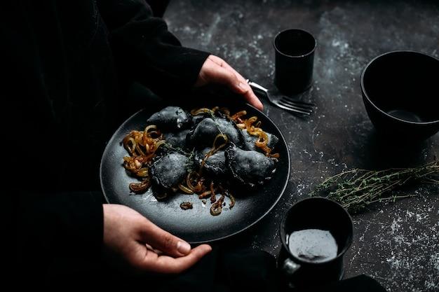 Bolinhos pretos com batatas e cebolas em um prato preto com fundo escuro