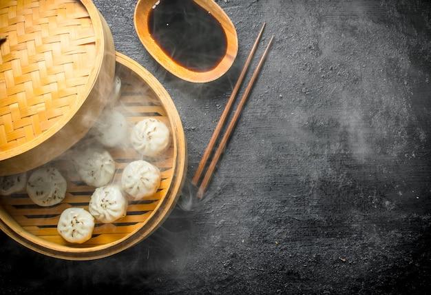 Bolinhos quentes de manta em um vaporizador de bambu com molho de soja em mesa preta rústica