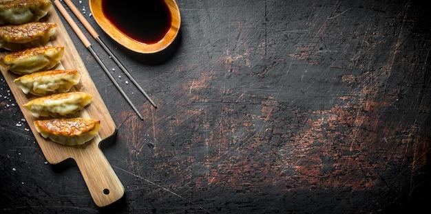 Bolinhos recém cozidos de gedza com molho de soja na mesa rústica escura.