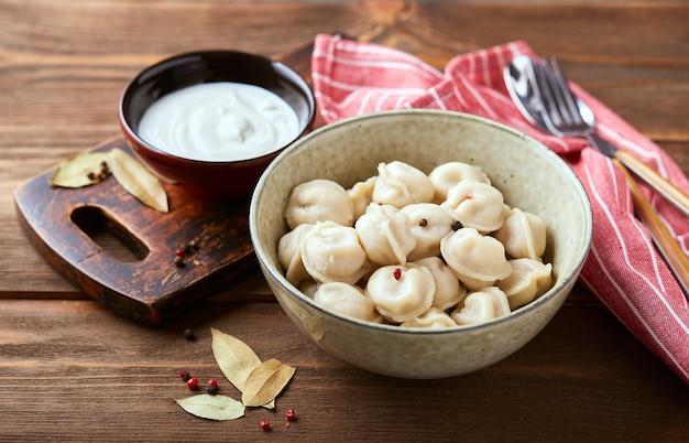 Bolinhos recheados com carne, pelmeni, ravióli, bolinhos. bolinhos de carne pelmeni russos tradicionais caseiros com creme de leite sobre fundo de madeira