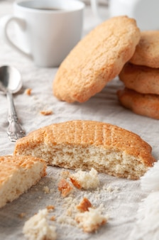 Bolinhos redondos de shortbread caseiros. quebrado ao meio. sobre uma toalha de mesa de linho de cor cinza. no fundo, há uma pilha de biscoitos. bule e caneca brancos.