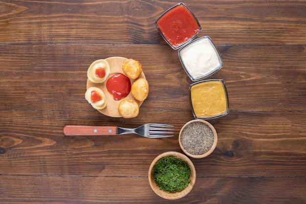 Bolinhos saborosos cozidos e fritos com condimentos na superfície de madeira.