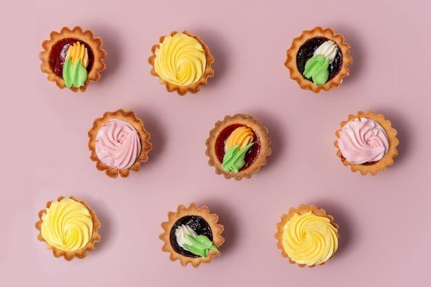 Bolinhos saborosos no fundo brilhante. cupcakes de baunilha com creme rosa e amarelo. padrão natural gostoso.
