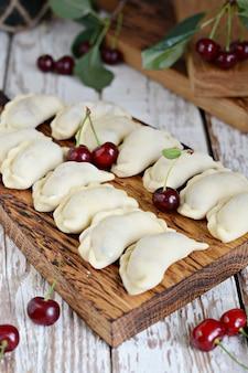 Bolinhos suculentos (vareniki) com cerejas frescas em uma tábua de madeira.