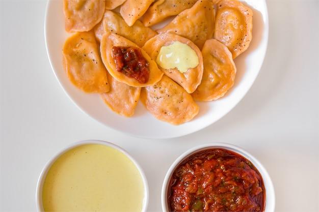 Bolinhos tradicionais de vareniki de comida russa e ucraniana com mostarda e molho de tomate em um prato branco.