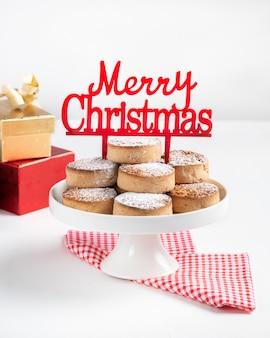 Bolinhos tradicionais do natal, nevaditos, com amêndoas e sésamo em de madeira branco com espaço da cópia.
