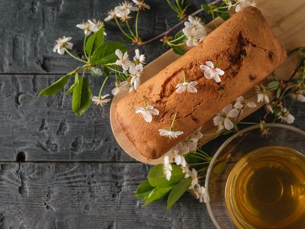 Bolo acabado de fazer com passas em flores de cerejeira e chá em uma mesa de madeira. bolos caseiros deliciosos. a vista do topo. postura plana.