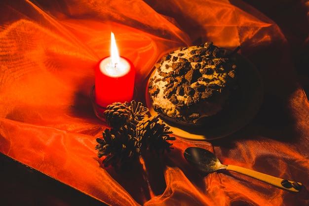 Bolo; acendeu vela e pinhas com colher em roupas vermelhas