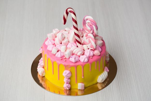 Bolo amarelo com glacê rosa e merengue