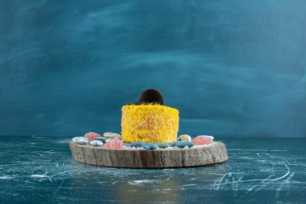 Bolo amarelo e pedras doces em uma placa em azul.