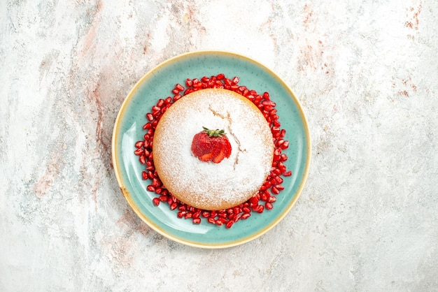 Bolo apetitoso prato de bolo azul com morangos e sementes de romã na mesa rosa