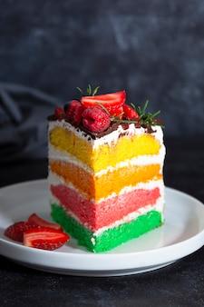 Bolo arco-íris com frutas frescas sobre fundo escuro.