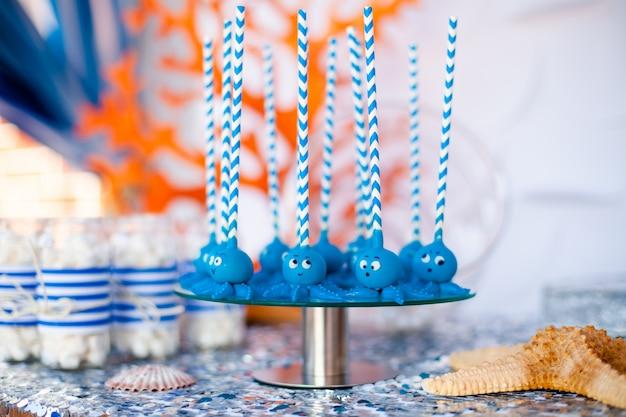 Bolo azul aparece polvos engraçados compartilhados no prato redondo de vidro e frascos com marshmallow.