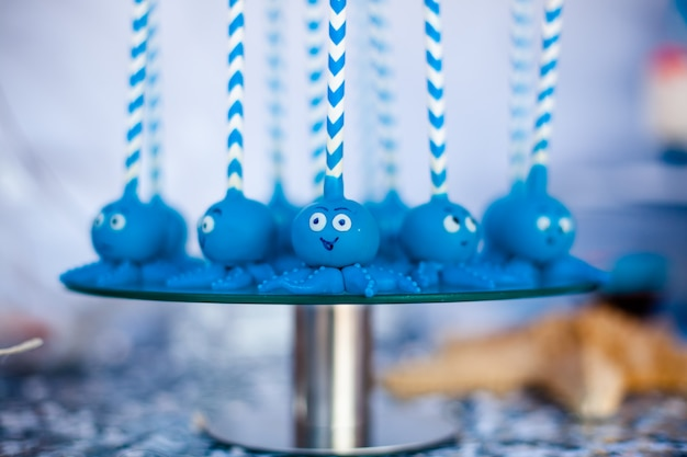 Bolo azul aparece polvos engraçados compartilhados no prato redondo de vidro.