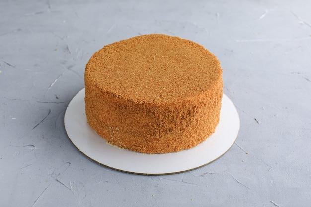 Bolo bolo de mel não cortado em uma entrega de confeitaria de fundo cinza de doces.