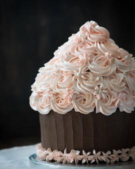 Bolo bonito do queque do aniversário com a decoração de creme cor-de-rosa.