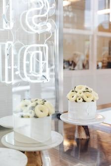 Bolo branco com as flores do creme da manteiga decoradas no carrinho na exposição.