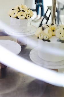 Bolo branco com as flores do creme da manteiga decoradas no suporte com a fuga clara no primeiro plano.