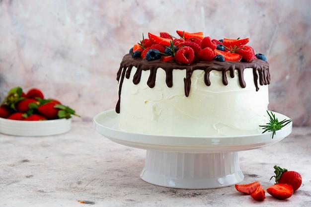 Bolo branco com cobertura de chocolate e frutas frescas.
