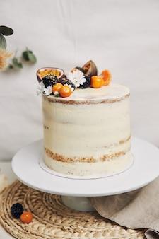 Bolo branco com frutas vermelhas e maracujá com plantas