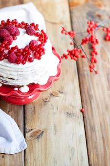 Bolo branco com frutas vermelhas e um galho em uma mesa de madeira