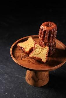 Bolo canele bordeaux, sobremesa francesa doce, sabores de rum e baunilha com centro de creme terno e crosta grossa caramelizada. sobre placa de madeira. fundo preto com espaço para cópia